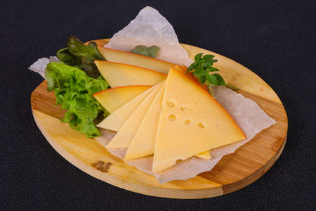 Sliced yellow Swiss cheese served salad leaves