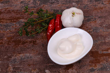 Mayonnaise sauce in the white bowl served thyme, red pepper and garlic