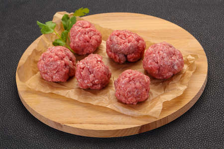 Raw meatball over wooden background ready for cooking 스톡 콘텐츠