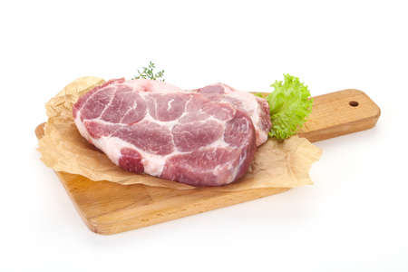 Raw pork steak over wooden board ready for cooking Imagens