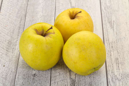 Yellow ripe apples over the wooden background
