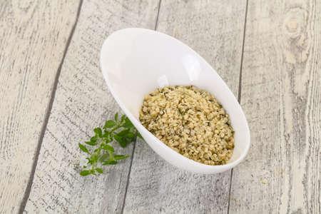 Peeled hemp seeds in the bowl over wooden background Reklamní fotografie