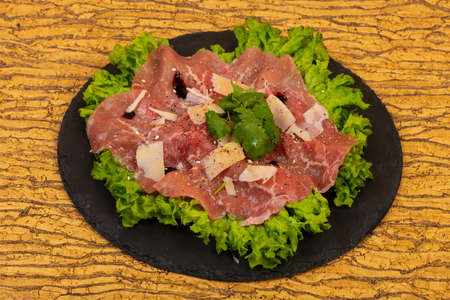 Beef carpaccio with parmesan cheese and salad leaves
