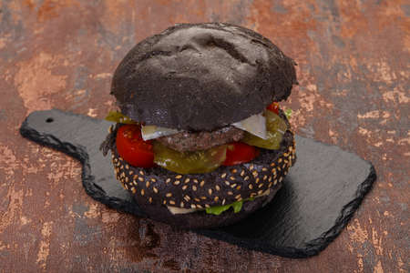 Tasty black burger with cheese and vegerables Stock Photo