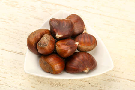 Chestnuts in the bowl over wooden background 写真素材