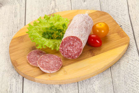 Italian dry Saliami pork sausage served salad leaves