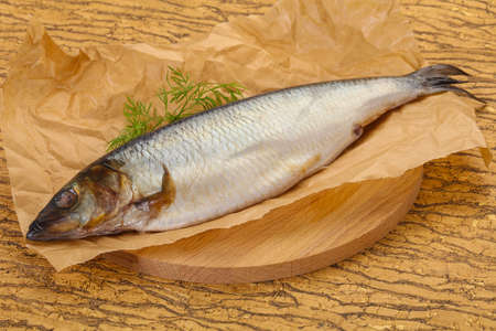 Salted herring over the wooden board with dill
