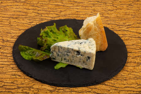 Blue cheese with salad leaves over board 免版税图像