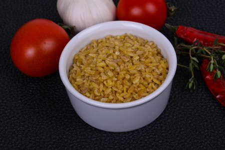 Raw golden bulgar in the bowl with tomatoes and garlic Foto de archivo