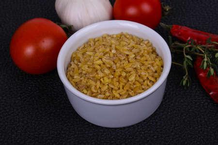 Raw golden bulgar in the bowl with tomatoes and garlic Zdjęcie Seryjne