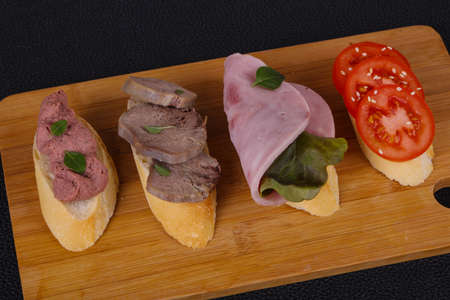 Brochette with tomato, ham and tongue served salad leaves and capers