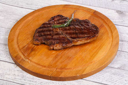 Ribeye steak with rosemary over the wooden board