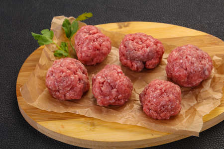 Raw meatball over wooden background ready for cooking Stock Photo
