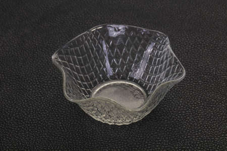 Empty glass bowl over black background