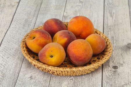 Ripe Peach heap in the wooden basket Foto de archivo