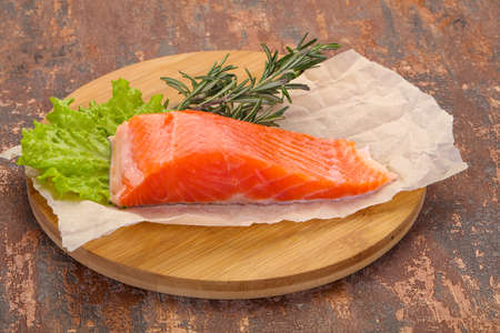 Piece of raw salmon over the wooden background