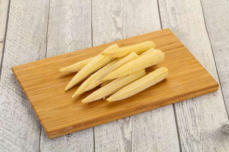 Raw baby corn over the wooden board