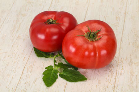 Ripe red tomato over wooden background
