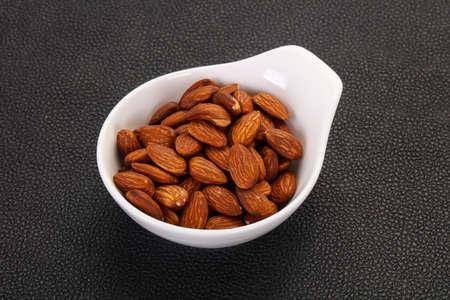 Almonds nuts heap in the bowl Banco de Imagens - 128602278