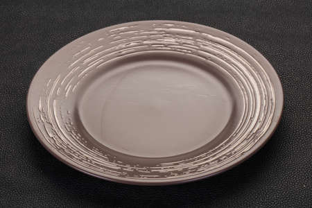 Empty ceramic plate over black background