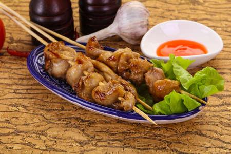 Chicken skin skewer with chili sauce Banco de Imagens - 128602289