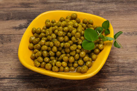 Canned Green peas in the bowl served leaves