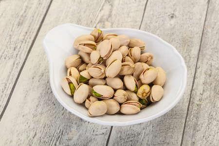 Pistachio nuts heap in the bowl Banco de Imagens - 128602710