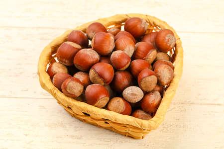 Hazelnut heap in the basket over wooden background