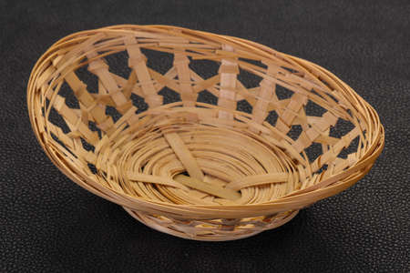 Empty wicker bowl over black background