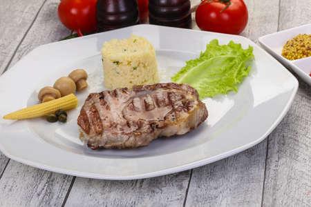 Grilled pork neck steak served pickled vegetables and couscous 版權商用圖片