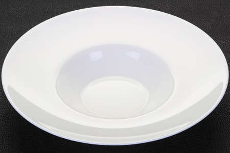 Empty white plate over black background