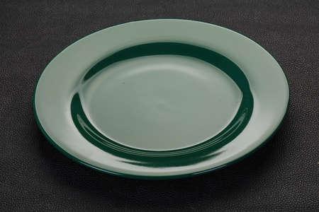 Empty ceramic plate over black background