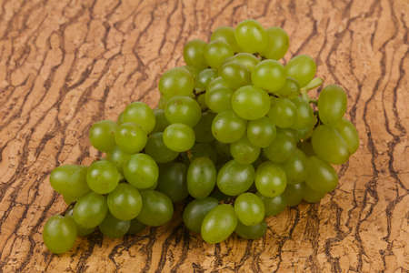 Sweet green grape branch over background