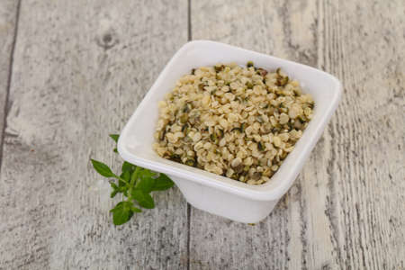 Peeled hemp seeds in the bowl over wooden background Imagens