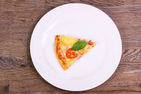 Pizza with ham and potato served basil