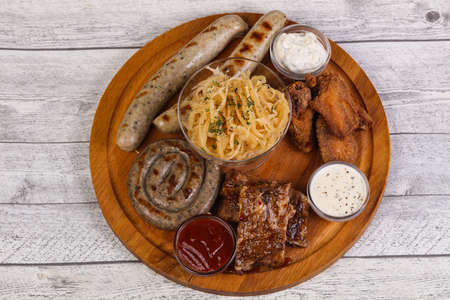 Meat plate with grilled sausages, ribs and chicken wings served cabbage