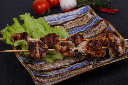 Pork kebab skewers in the plate with salad leaves and tomatoes served thyme and garkic Stock Photo
