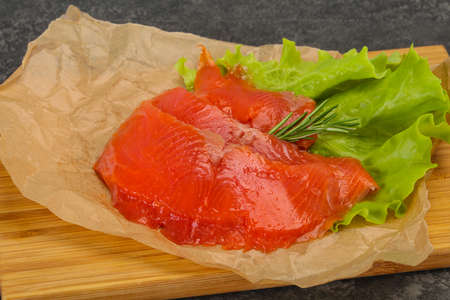 Sliced salmon fillet snack served rosemary