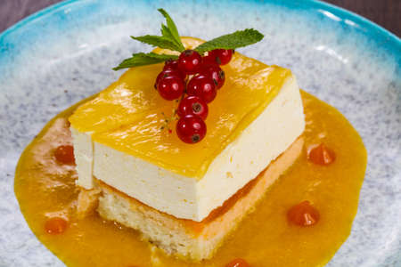 Traditional Cheesecake with orange sauce served red currants