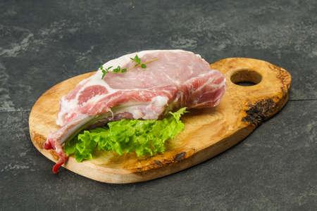 Raw pork bone steak over wooden background 版權商用圖片 - 129176302