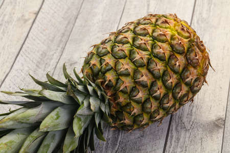Fresh ripe Pineapple over the wooden background