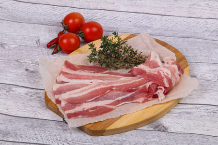 Raw bacon on the board served thyme