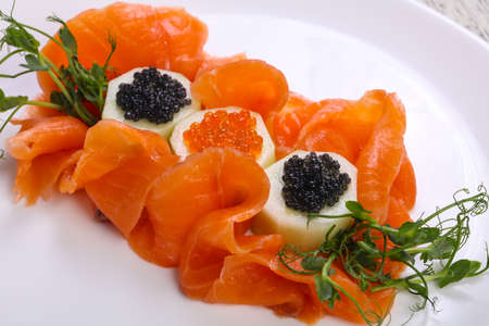 Sliced salmon with red and black caviar
