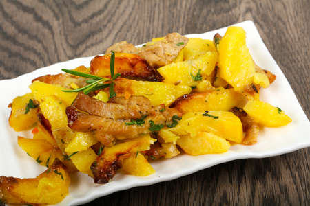 Fried potato with pork served rosemary