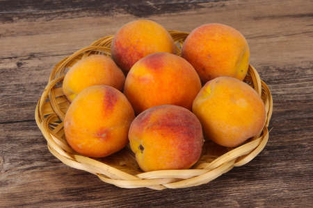 Ripe Peach heap in the wooden basket Stock fotó