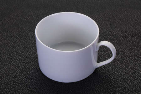 Empty ceramic cup over black background