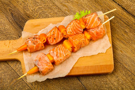 Raw salmon skewer with spices ready for cooking Фото со стока