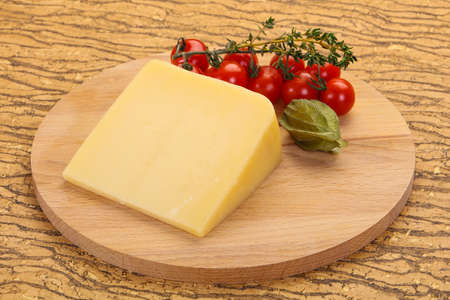 Hard parmesan cheese piece over wooden background