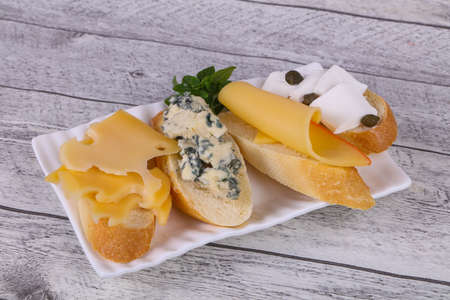 Bruschetta with various cheeses served basil leaves and capers Imagens