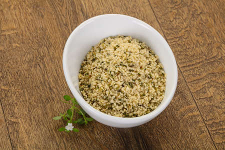 Peeled hemp seeds in the bowl over wooden background 写真素材